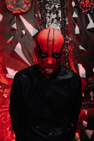 halloween make up. scary person ready for party. man with a false bald head and red demon makeup on his head in black gothic studio. 免版税图像 - 132796555