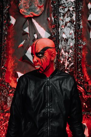 halloween make up. scary person ready for party. man with a false bald head and red demon makeup on his head in black gothic studio. 免版税图像