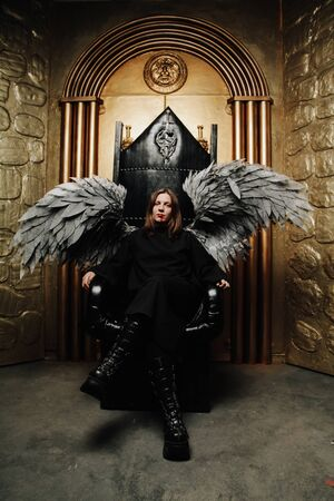 Dark Angel man with huge wings in black outfit sitting on the throne on golden gates background alone Standard-Bild