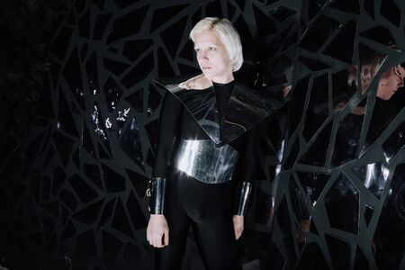 young blonde caucasian man standing in alien cosmos halloween costume and looking near the many mirrors and reflecting on black background