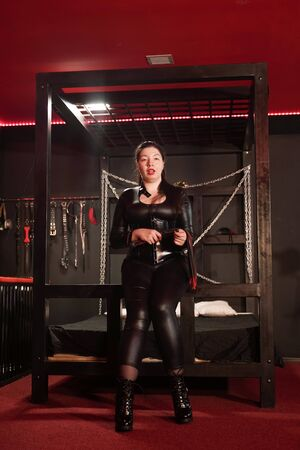 Sensual woman in black latex costume with leather whip in room