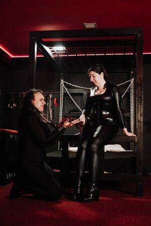 Sensual mujer asiática de talla grande en traje de látex negro juega con su esclavo en la habitación Foto de archivo