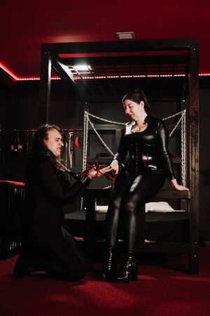 Sensual plus size asian woman in black latex costume plays with her slave in room Stock Photo