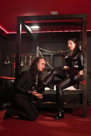 Sensual mujer asiática de talla grande en traje de látex negro juega con su esclavo en la habitación