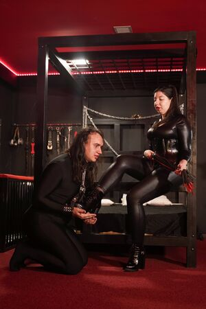 Sensual plus size asian woman in black latex costume plays with her slave in room