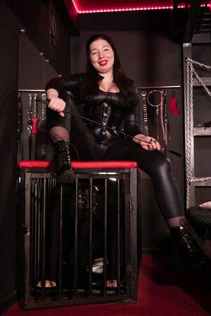 Une femme asiatique sensuelle de grande taille en costume de latex noir joue avec son esclave dans la chambre