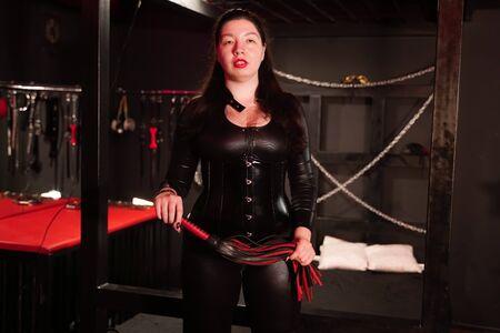 Femme sensuelle en costume de latex noir avec fouet en cuir dans la chambre