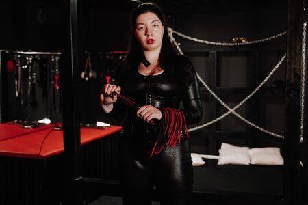 Sinnliche Frau im schwarzen Latexkostüm mit Lederpeitsche im Zimmer Standard-Bild