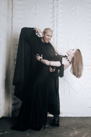 young vampire love couple in black halloween costumes ready for the party. man and woman bite and enjoy each other on white background.