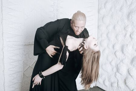young vampire love couple in black halloween costumes ready for the party. man and woman bite and enjoy each other on white background. 版權商用圖片
