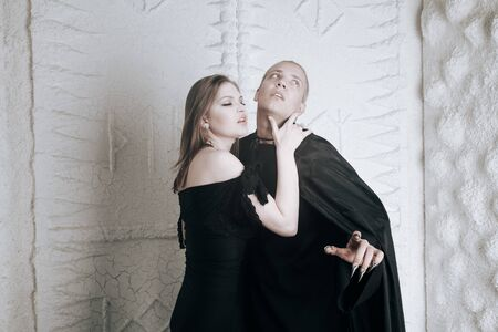 young vampire love couple in black halloween costumes ready for the party. man and woman bite and enjoy each other on white background. Banque d'images
