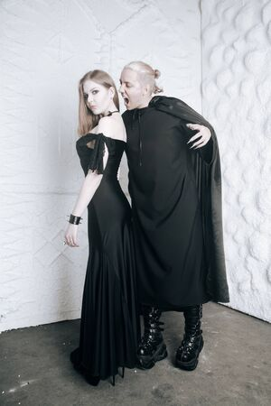 young vampire love couple in black halloween costumes ready for the party. man and woman bite and enjoy each other on white background. Stock Photo