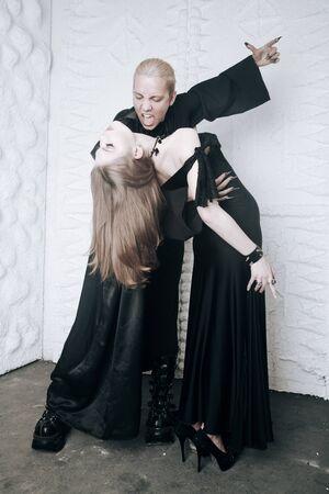 jeune couple d'amour de vampire en costumes d'halloween noirs prêts pour la fête. l'homme et la femme se mordent et s'amusent sur fond blanc.