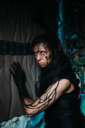 man with tree makeup for halloween party on his face and hands poses at night against a wooden gate in cyan color smoke
