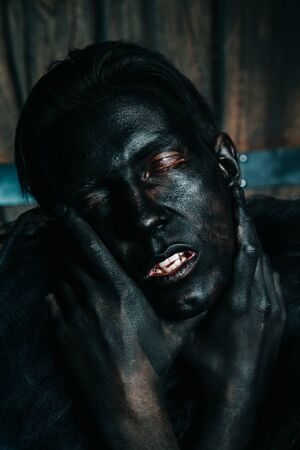 young caucasian man with white skin painted his face and hands to black color and love it. close up halloween portrait.