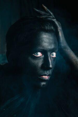 un jeune homme de race blanche à la peau blanche a peint son visage et ses mains en noir et l'aime. gros plan portrait d'halloween.