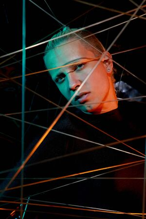 a teenager at a party got tangled up among the ropes. young man in depression in the light of the neon on black background Stock Photo