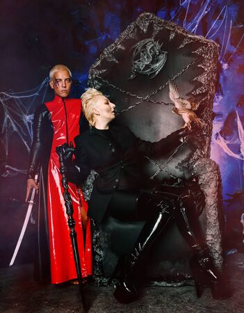 Gothic couple with little bird on a huge scary throne ready for Halloween party