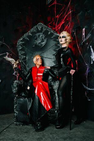 Amis gothiques avec un maquillage sombre dans des tenues rock sur un énorme trône effrayant prêt pour la fête d'Halloween
