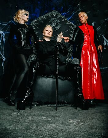 Gothic 3 friends in dark costumes with make up on a huge scary throne ready for Halloween party