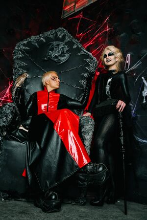 Gothic friends with dark make up in rock outfits on a huge scary throne ready for Halloween party
