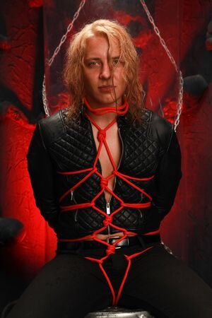 handsome young long-haired guy sits in a leather jacket and is tied with red ropes. slave lobes and be dominated