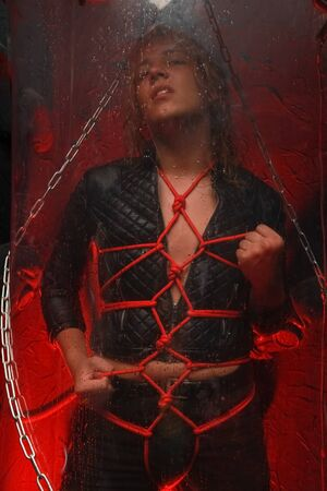 sweet blond male captive is tied up with red ropes and stands in a transparent space tube ready for a party as slave