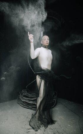 strange guy in tight beige leotard with dust on black studio background