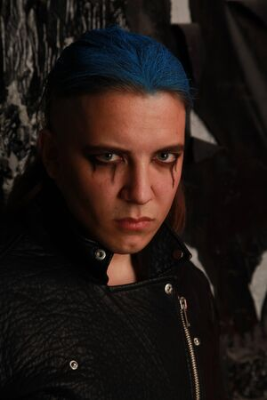Teen alt boy with blue hair and shaved head dressed in black on dark background