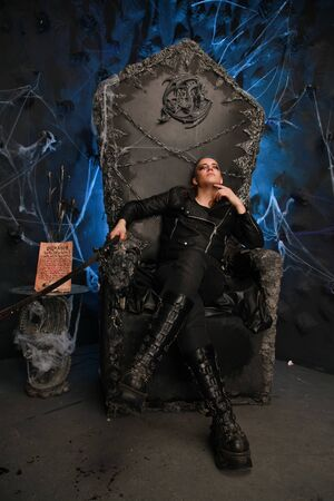 alternative fashioned young man sitting on the satan throne in dark background alone