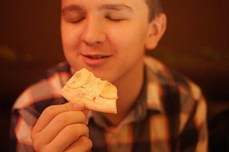 teen boy eats pizza and enjoys it, closeup enjoying and savoring. Zdjęcie Seryjne