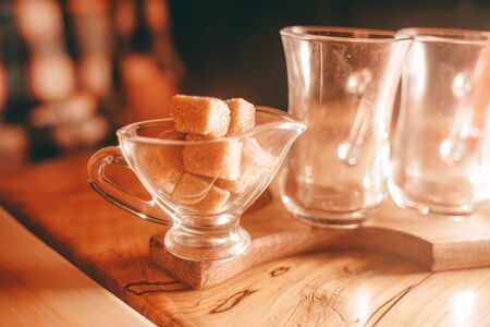 a Cup of clear glass tea, a small sugar bowl with a square of yellow sugar, and a teapot of tea on the wooden table Stock Photo