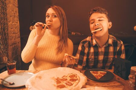 happy pregnant woman with teenager boy eating pizza and enjoy it with savor. friends loves fast food. dinner in the pizzeria. Zdjęcie Seryjne