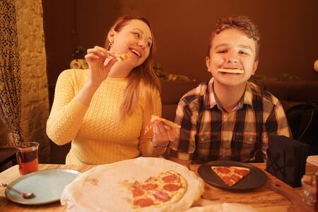 happy pregnant woman with teenager boy eating pizza and enjoy it with savor. friends loves fast food. dinner in the pizzeria. Zdjęcie Seryjne - 133293206