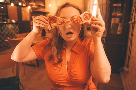 pretty plus size caucasian woman savoring and enjoying pizza in the pizzeria Zdjęcie Seryjne - 133293209