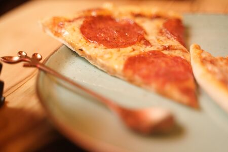 slice delicious fresh homemade pizza on a plate on the table. classic pizza peperroni with sausage.