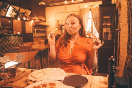 pretty plus size caucasian woman savoring and enjoying pizza in the pizzeria