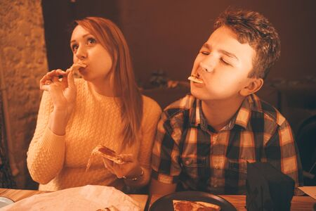 happy pregnant woman with teenager boy eating pizza and enjoy it with savor. friends loves fast food. dinner in the pizzeria. Zdjęcie Seryjne - 133293218