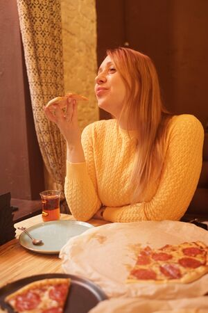 happy caucasian blonde plus size woman eating pizza end savoring with enjoy Zdjęcie Seryjne - 133293219