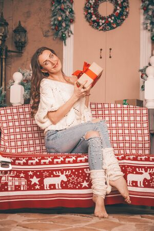 charming thin girl in fashionable jeans embroidered with pearls and Christmas sweater barefoot sitting on a bench, full length body
