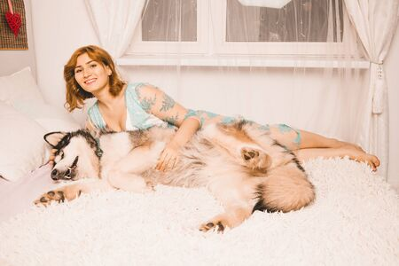 charming plus size girl with red hair in a nightgown posing with her large dog, a Malamute best friend in white bed in the bedroom Zdjęcie Seryjne - 133819614