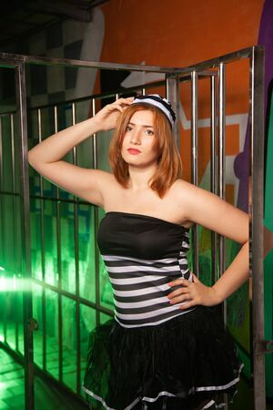 sweet plus size woman in a carnival striped inmate costume stands near the prison cage and is sad in the green smoke 스톡 콘텐츠 - 133820017
