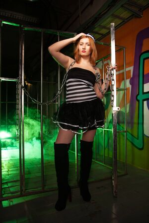 sweet plus size woman in a carnival striped inmate costume stands near the prison cage and is sad in the green smoke 스톡 콘텐츠