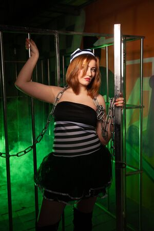 sweet plus size woman in a carnival striped inmate costume stands near the prison cage and is sad in the green smoke 스톡 콘텐츠 - 133820037