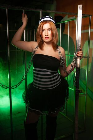 sweet plus size woman in a carnival striped inmate costume stands near the prison cage and is sad in the green smoke 스톡 콘텐츠 - 133820039