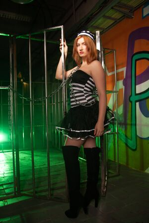 sweet plus size woman in a carnival striped inmate costume stands near the prison cage and is sad in the green smoke 스톡 콘텐츠 - 133820046