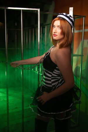 sweet plus size woman in a carnival striped inmate costume stands near the prison cage and is sad in the green smoke 스톡 콘텐츠 - 133820049
