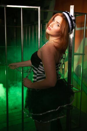 sweet plus size woman in a carnival striped inmate costume stands near the prison cage and is sad in the green smoke 스톡 콘텐츠 - 133820048