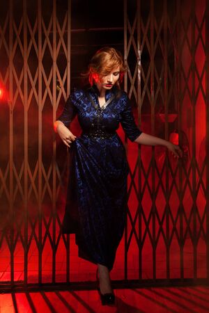 The red haired plus size woman in evening long dress and leather harness standing near big gates in a black alley in night