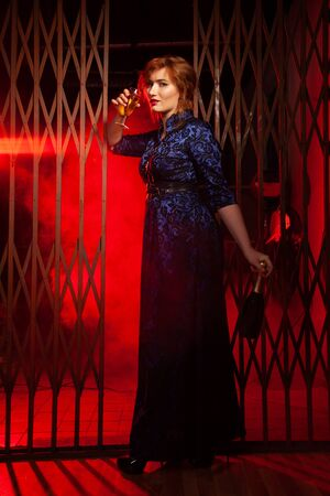a woman stands in an evening dress with a glass of alcohol in a dark night alley after a party